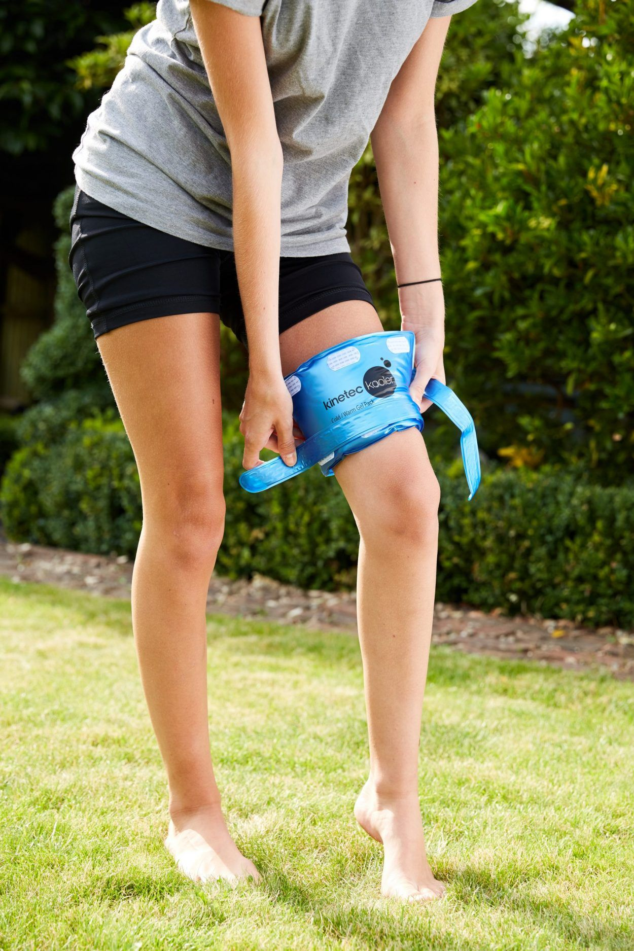 Cold pack strapped knee Female being strapped on Garden LR scaled